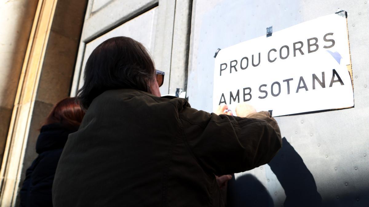 Un home enganxant cartells a les portes de l'Arquebisbat de Tarragona en la protesta per denunciar els abusos sexuals a menors