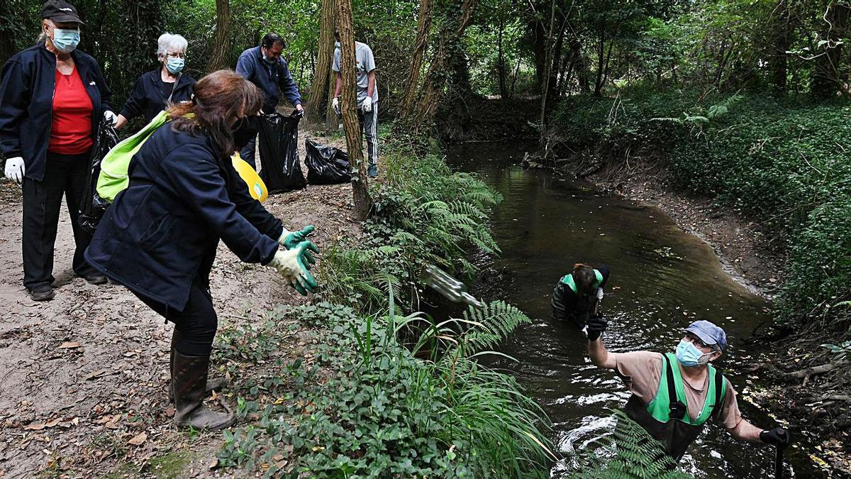 Uno de los grupos de voluntarios retira residuos del cauce del Gafos.     // GUSTAVO SANTOS