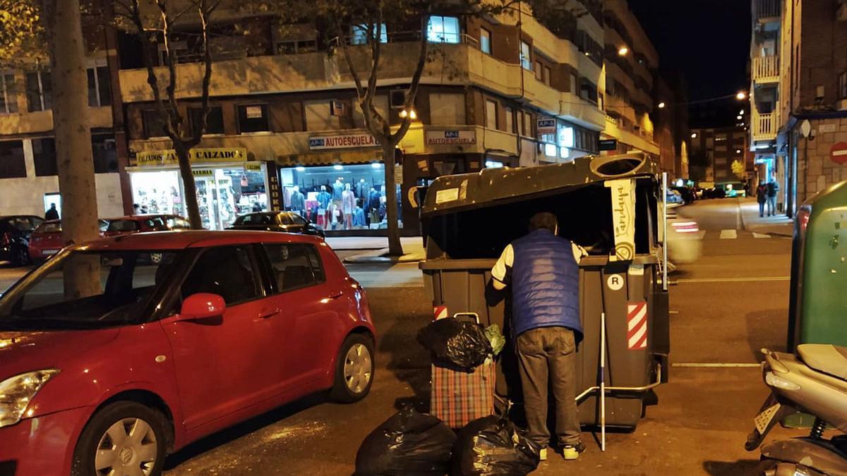 Un ciudadano rebusca en las basuras.  