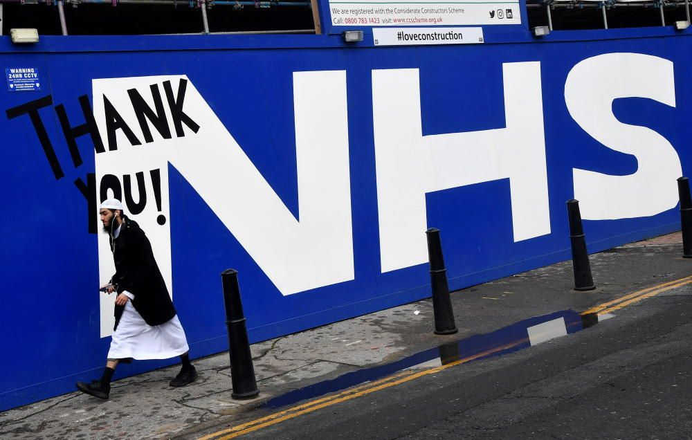 A man walks past a mural thanking British health ...