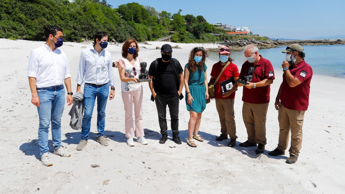 La conselleira Ángeles Vázquez muestra uno de los Premios Mestre Mateo junto a Alfonso Zarauza y Paula Cons.