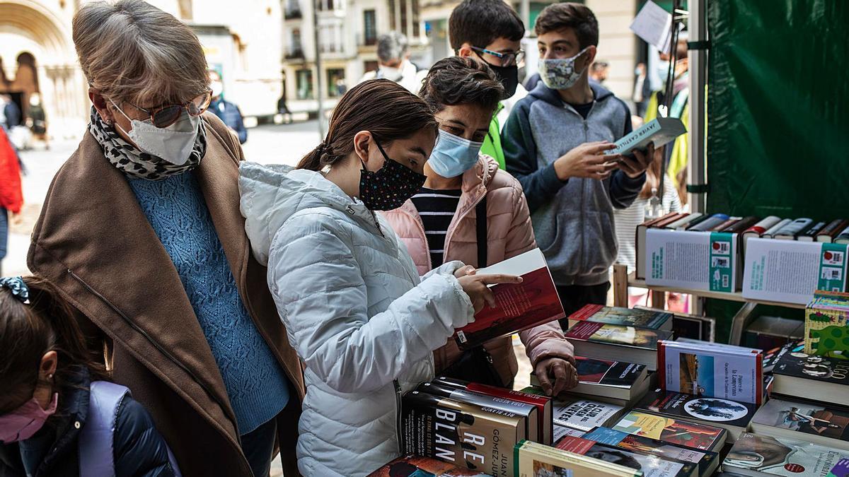 Varios clientes observan algunos de los libros de uno de los establecimientos de la feria.