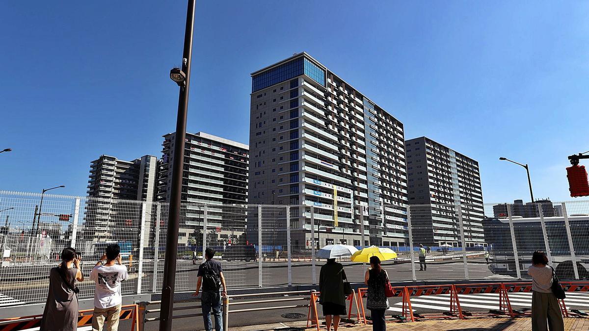 Varias personas observan desde la distancia los edificios que componen la villa olímpica de Tokio. // EFE