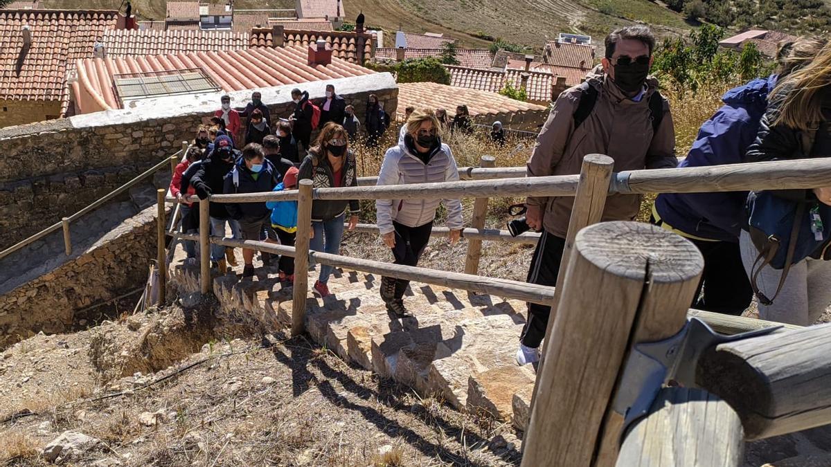 Decenas de turistas suben por la escalera que conduce al castillo de Culla.