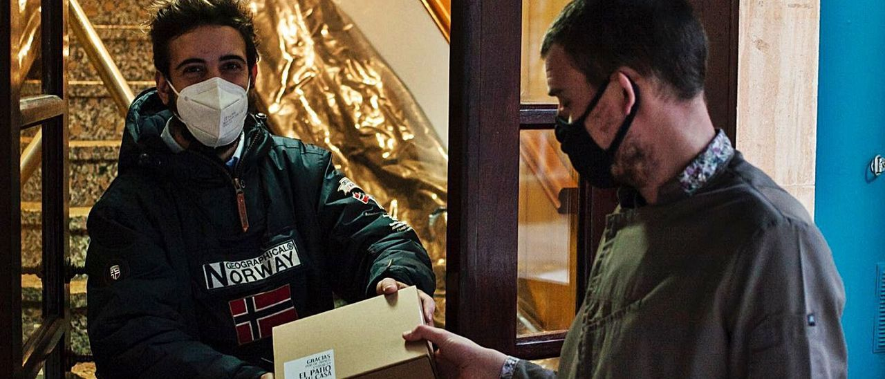 Manuel Cano, a la izquierda, recibiendo un pedido a domicilio. | R. A. I.