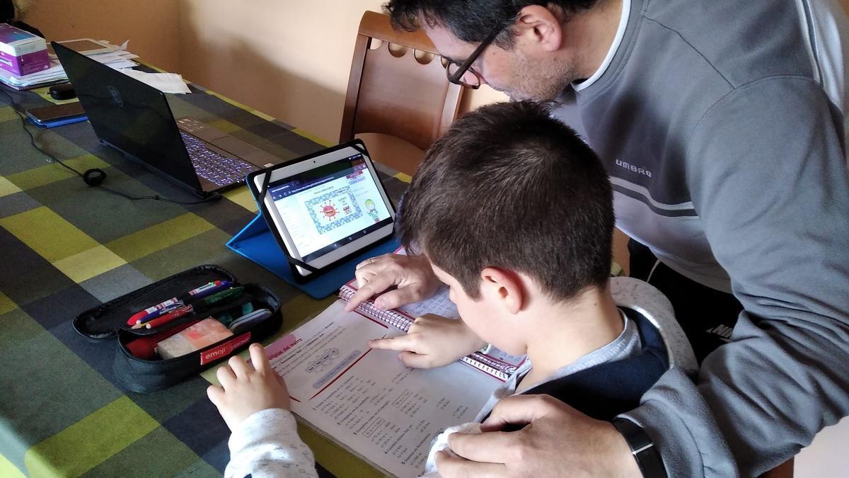 Padre e hijo realizan las tareas escolares juntos