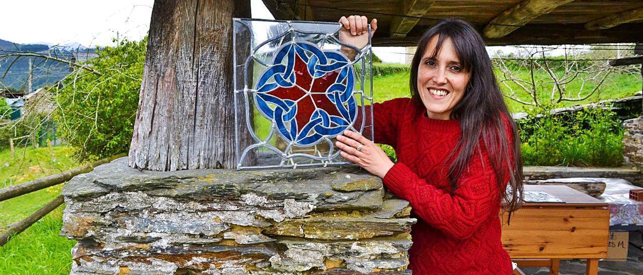 Isaura Tejo muestra uno de sus trabajos con el vidrio bajo el hórreo de la casa donde vive.  Ana Paz Paredes.
