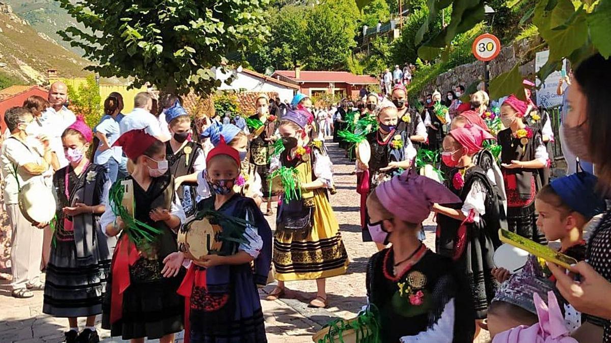 Arriba, un momento de la procesión, con la imagen tras los mozos. Sobre estas líneas, participantes en los actos, ataviadas con los trajes típicos.