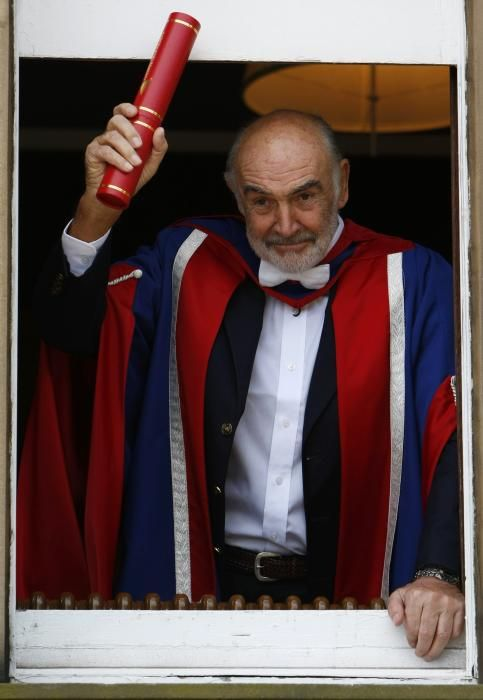 Actor Sean Connery holds a scroll as he poses ...