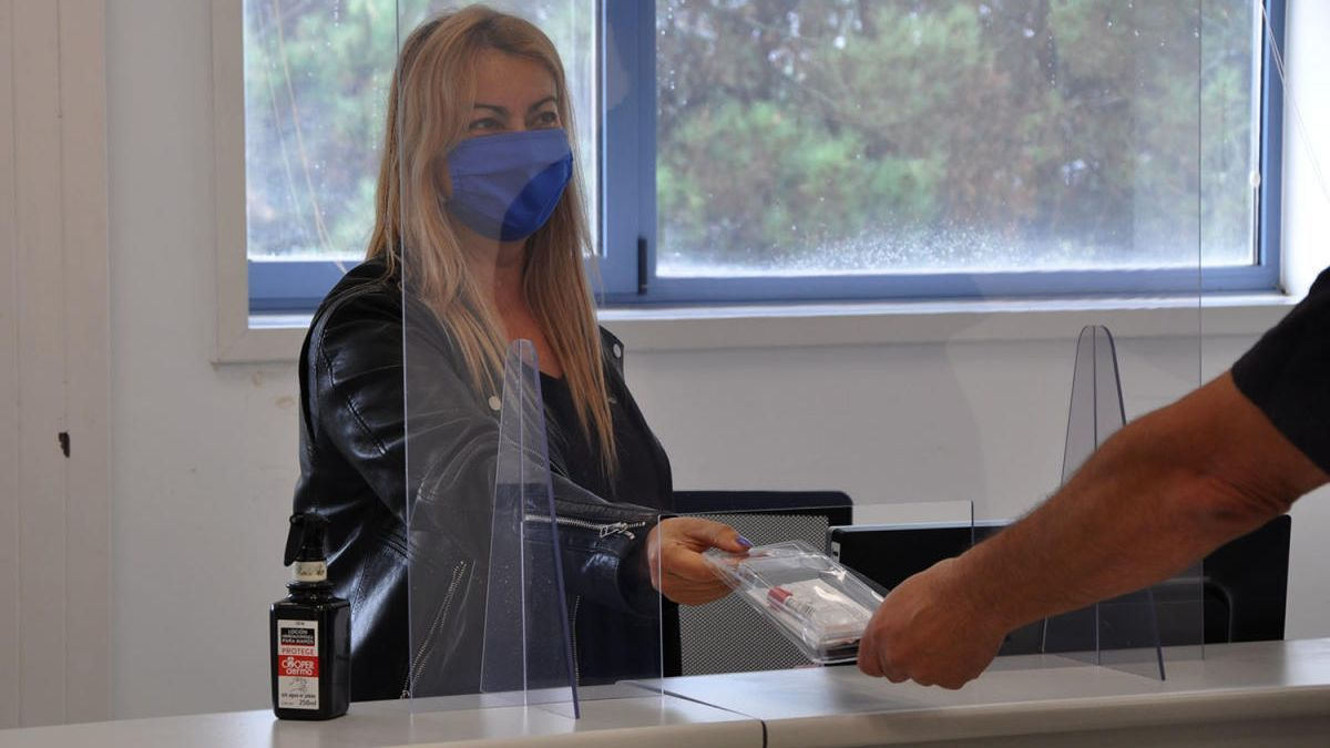 Una trabajadora recoge un test de saliva. // Duvi