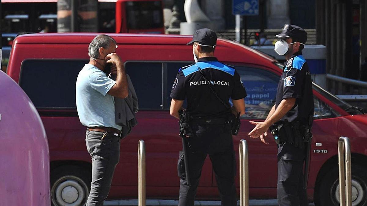 Dos agentes de la Policía Local hablan con un hombre en la calle. |  // L. O.