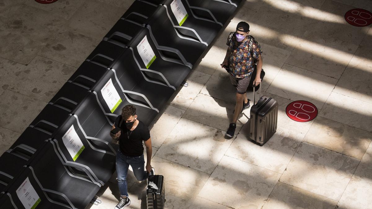 Dos personas con maletas en la terminal T4 del Aeropuerto Adolfo Suárez Madrid-Barajas.