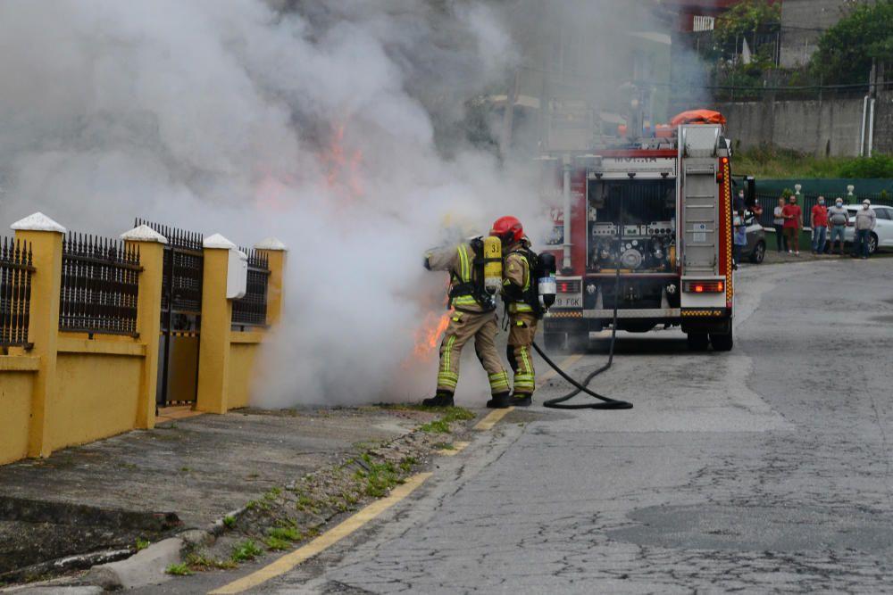 Los bomberos extinguiendo el fuego del vehículo que quedó completamente calcinado / G. Núñez