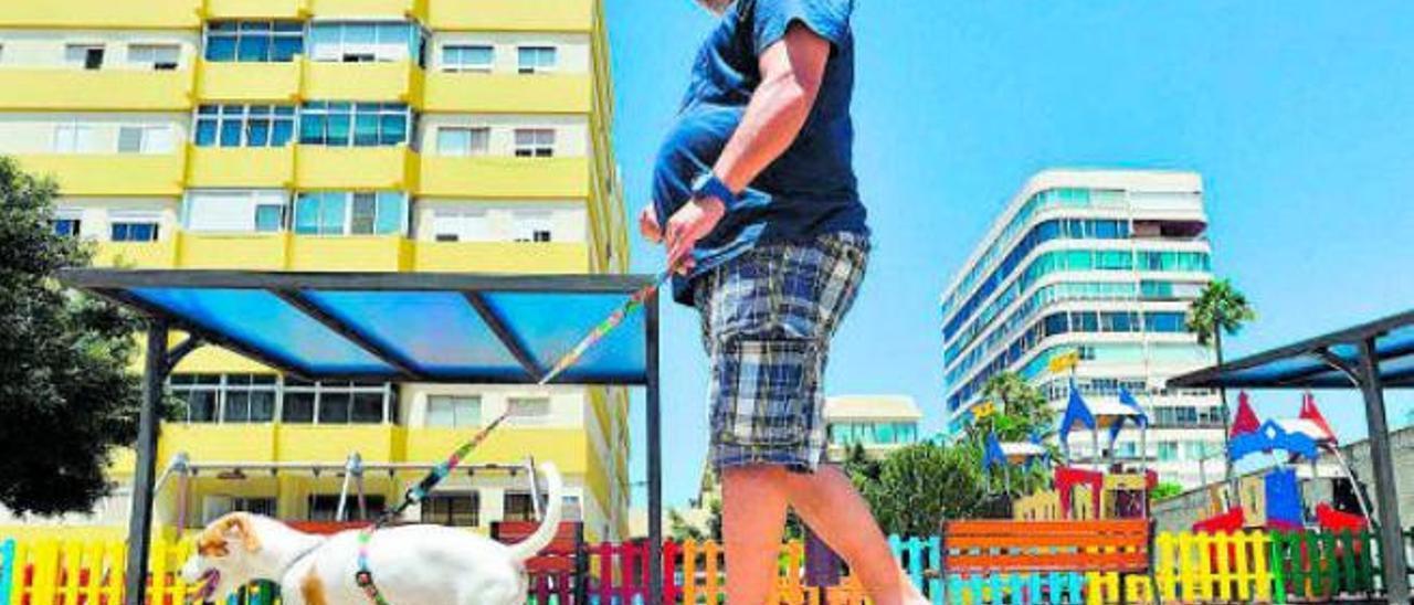 Un hombre pasea a su perro por el parque Lorenzo Godoy, zona donde los vecinos demandan un pipican.