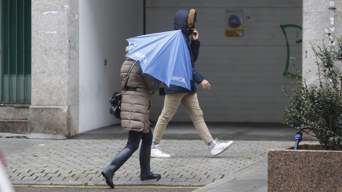 Una mujer trata de protegerse de a lluvia, esta mañana en Vigo