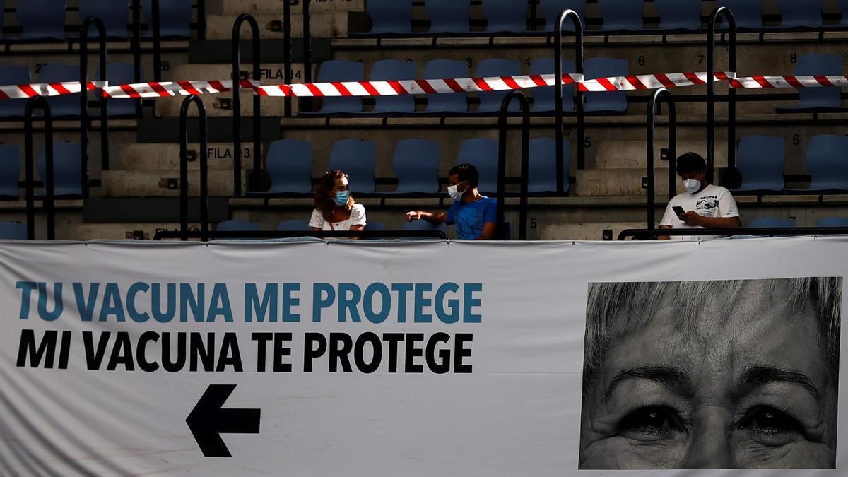 Varias personas esperan su turno de vacunación en la plaza de toros de San Sebastián.