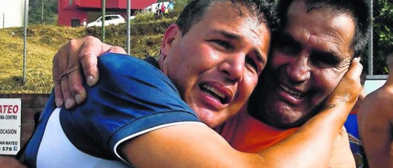 El entrenador del Panadería Pulido y exjugador de la UD Socorro (i), emocionado, abraza a Juan Sosa, tras conquistar el ascenso a Tercera en San Mateo.