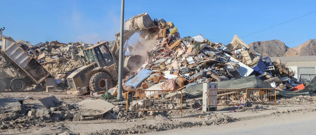 Un camión descarga los enseres recogidos en las calles de Orihuela mientras una retroexcavadora los amontona en la campa del polígono industrial Puente Alto.