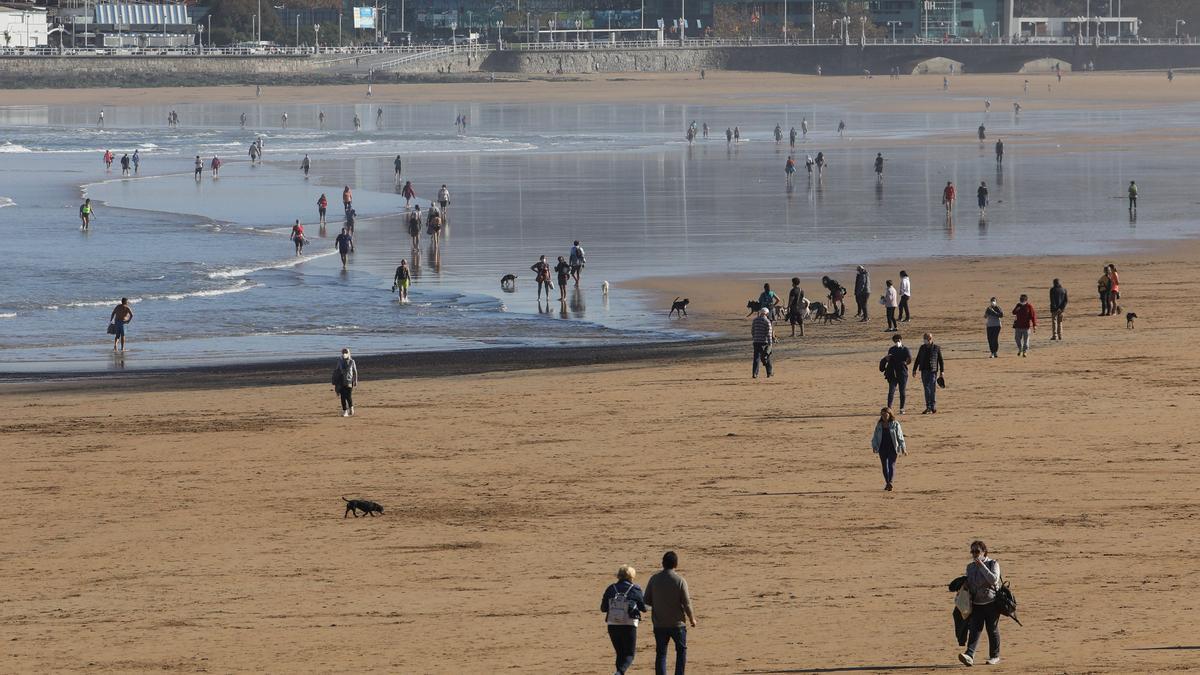Paseantes por la arena de la playa de San Lorenzo.