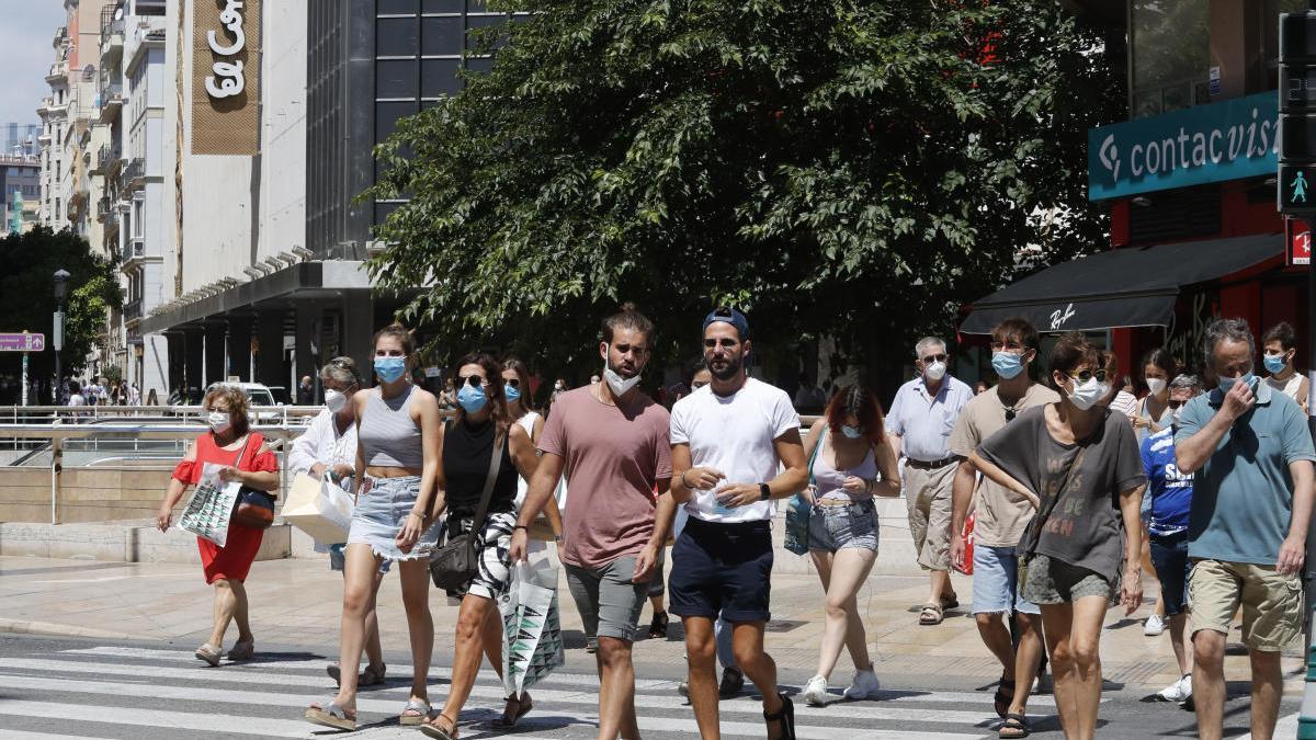 Un grupo de jóvenes paseando por la calle Colón el primer día de obligación de llevar mascarilla.