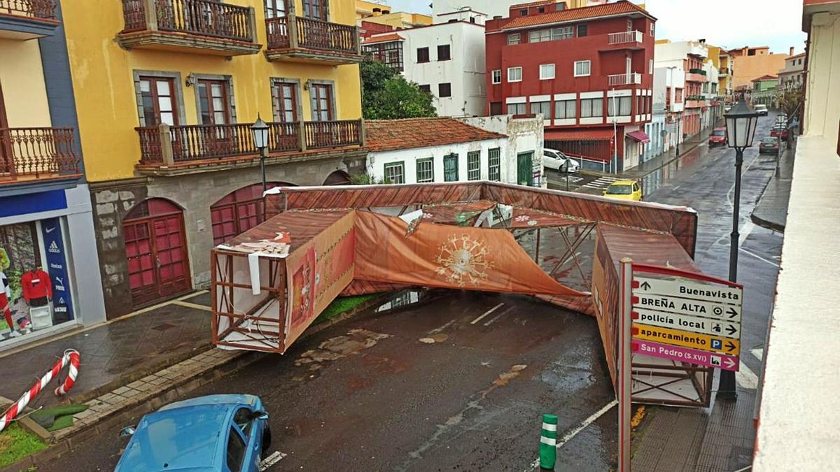 Desperfectos provocados por el viento en Breña Alta (arriba), la lluvia corriendo en las calles de El Médano y la playa de Tazacorte ayer | |