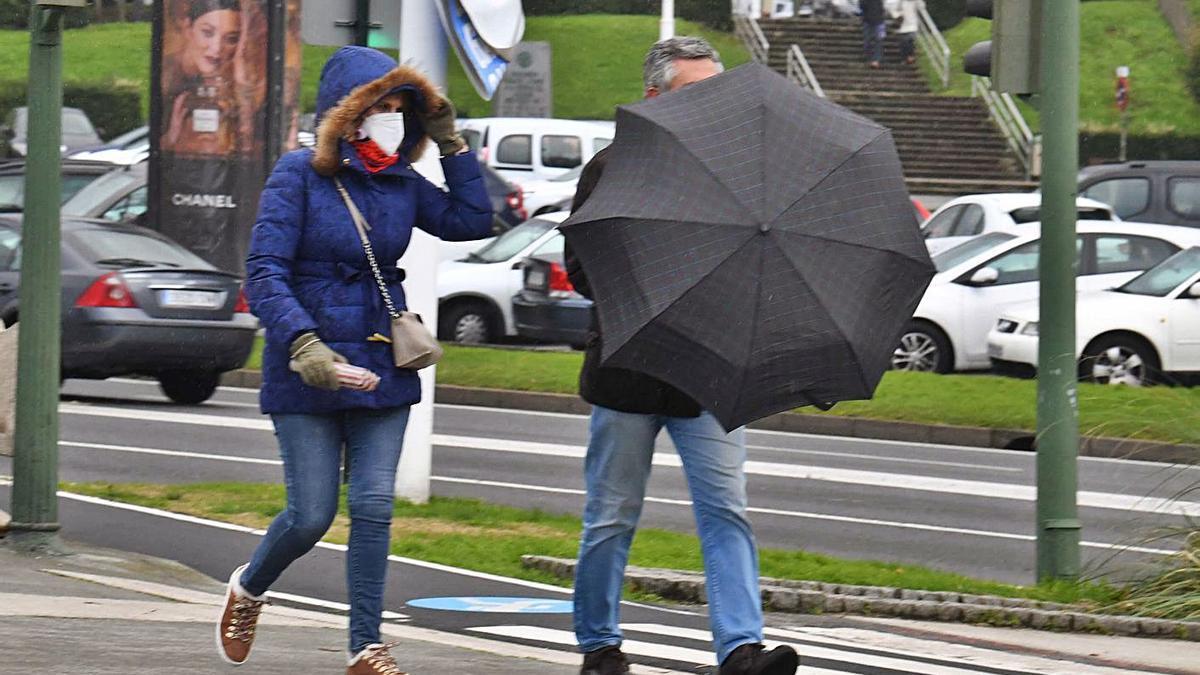 Viandantes se protegen del frío y la lluvia en A Coruña, que ayer registró 2,8º de mínima. |   // VÍCTOR ECHAVE