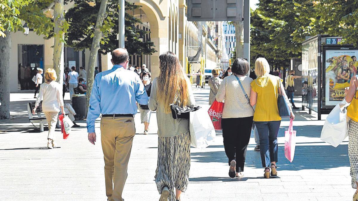 Dos parejas pasean con bolsas de compra por el paseo de la Independencia de Zaragoza