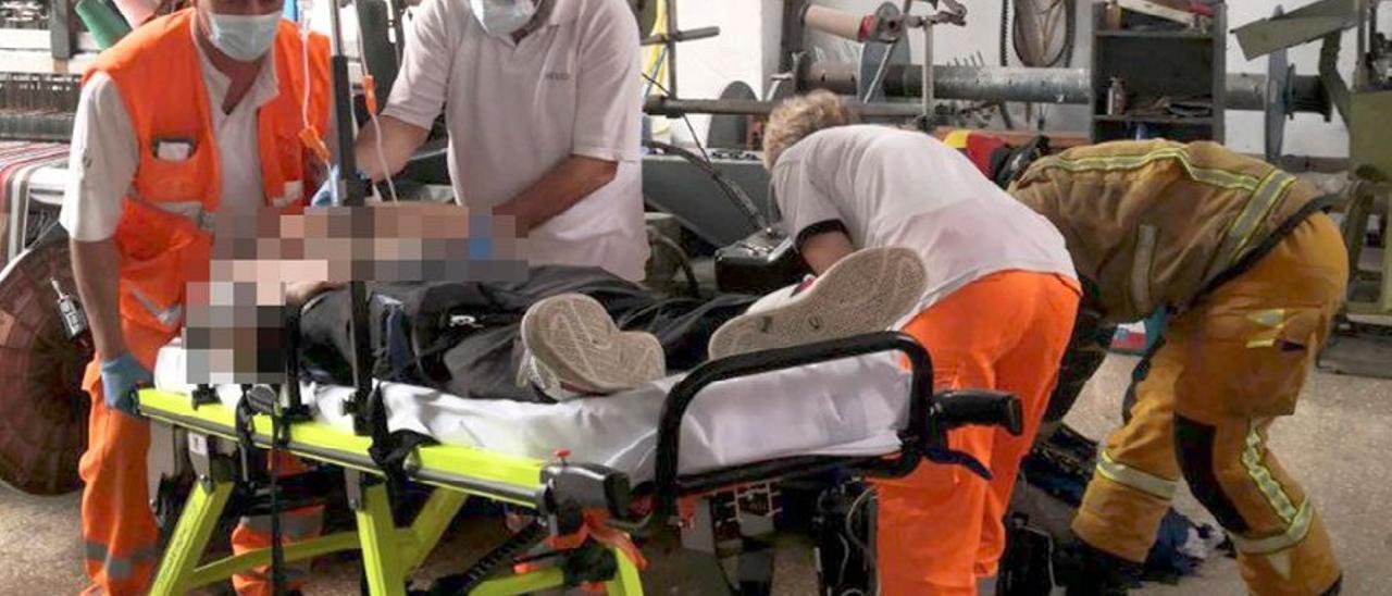 Los servicios sanitarios trasladando al trabajador accidentado.