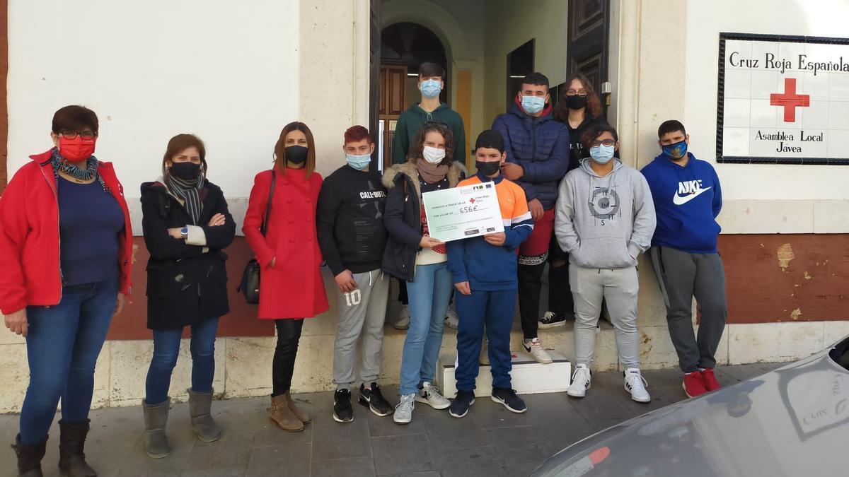 Los alumnos, los profesores y la directora del Antoni Llidó al realizar la donación en la Cruz Roja