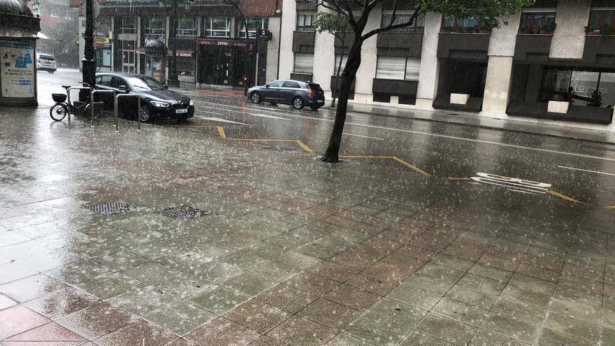 Otra tormenta de verano sobre Oviedo: la lluvia sorprende a los viandantes en la zona centro de la región