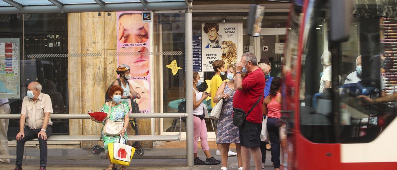 Viajeros esperan un autobús urbano, en la ciudad de Alicante