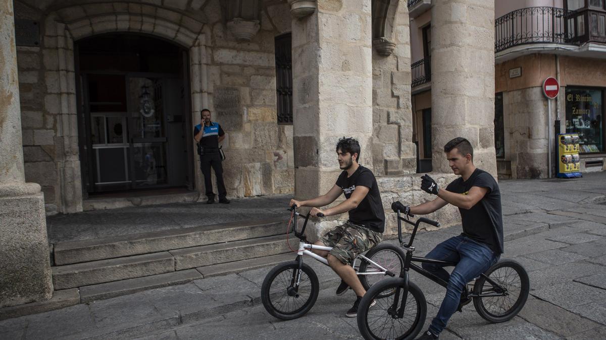 Dos jóvenes en bicicleta por la Plaza Mayor de Zamora