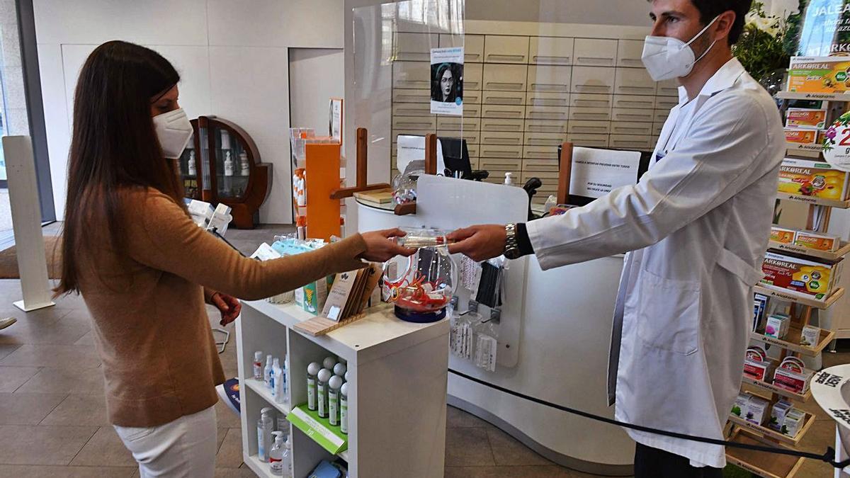 Un farmacéutico entrega un kit para el test de saliva en su farmacia. |   // VÍCTOR ECHAVE