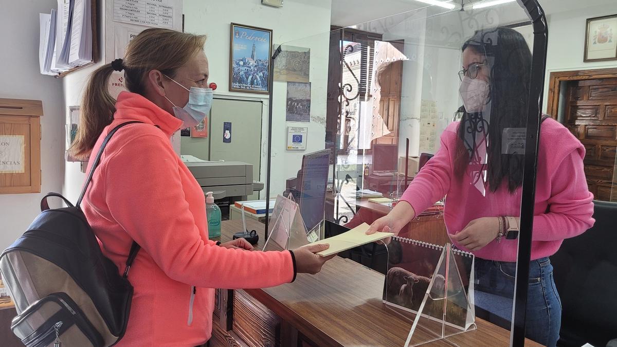 Una vecina recoge su libro en el Ayuntamiento de Pedroche.