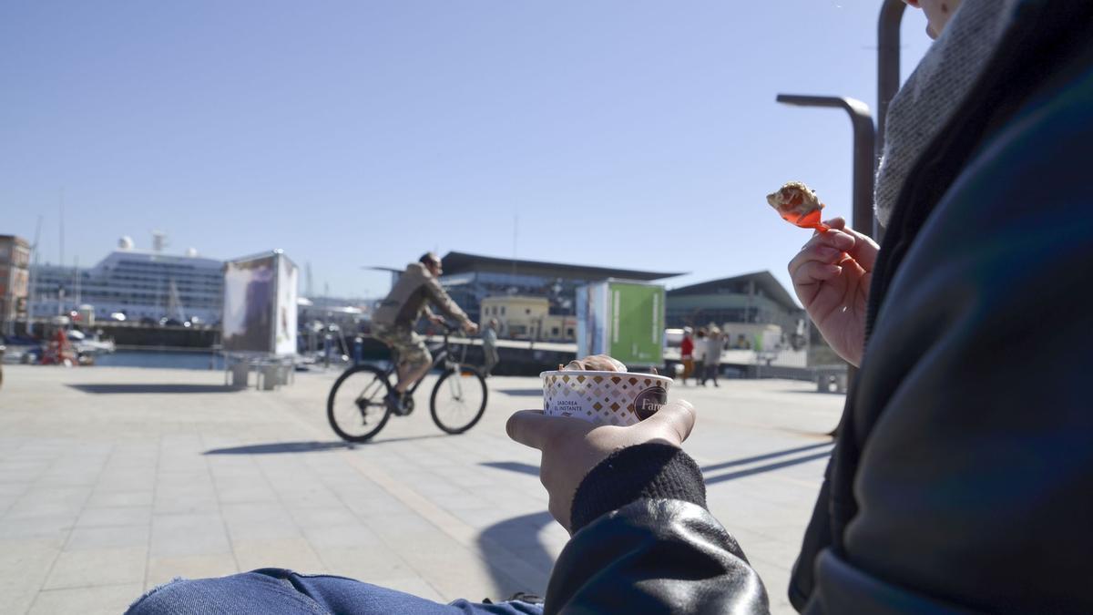 Una persona degusta un helado en la Marina de A Coruña.