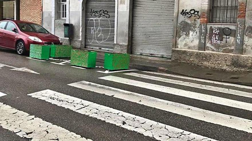 Jardineres en lloc de motos en un aparcament del carrer de la Caritat