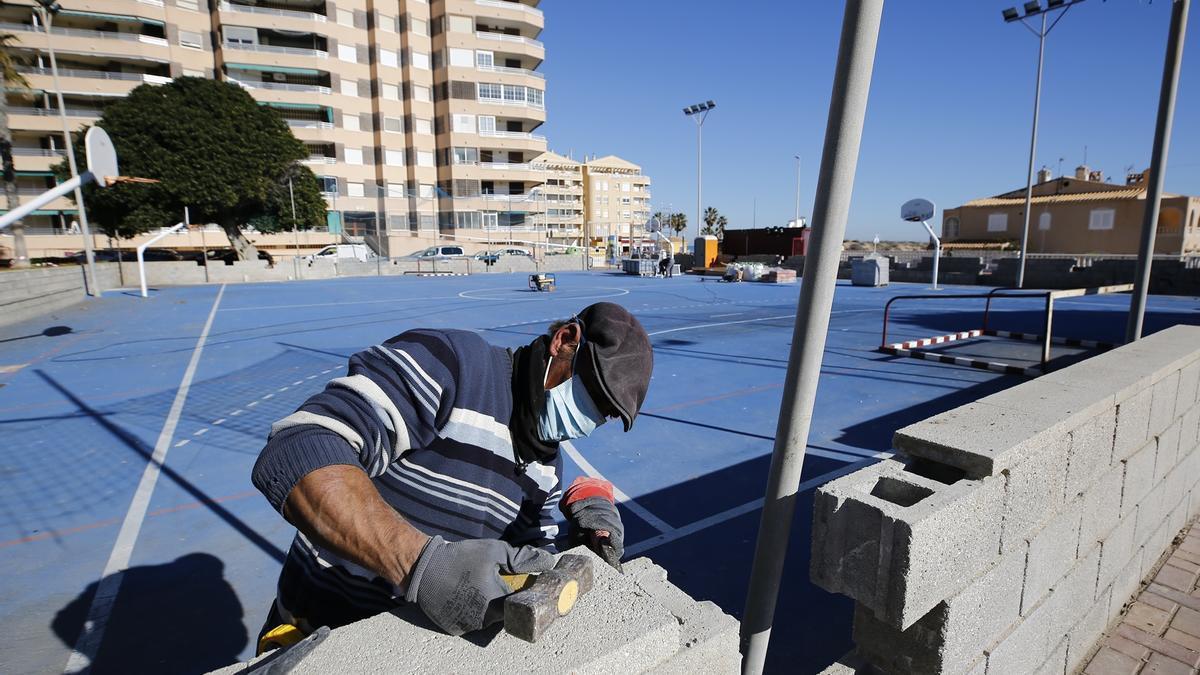 Imagen de un operario en los trabajos de reparación de la pista polideportiva de La Mata