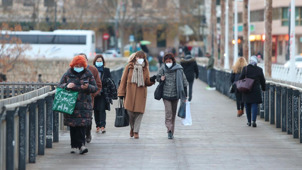 Varias personas cruzan el 'Pont de Fusta' abrigados contra el frío y protegidos contra el coronavirus en Valencia con mascarillas.