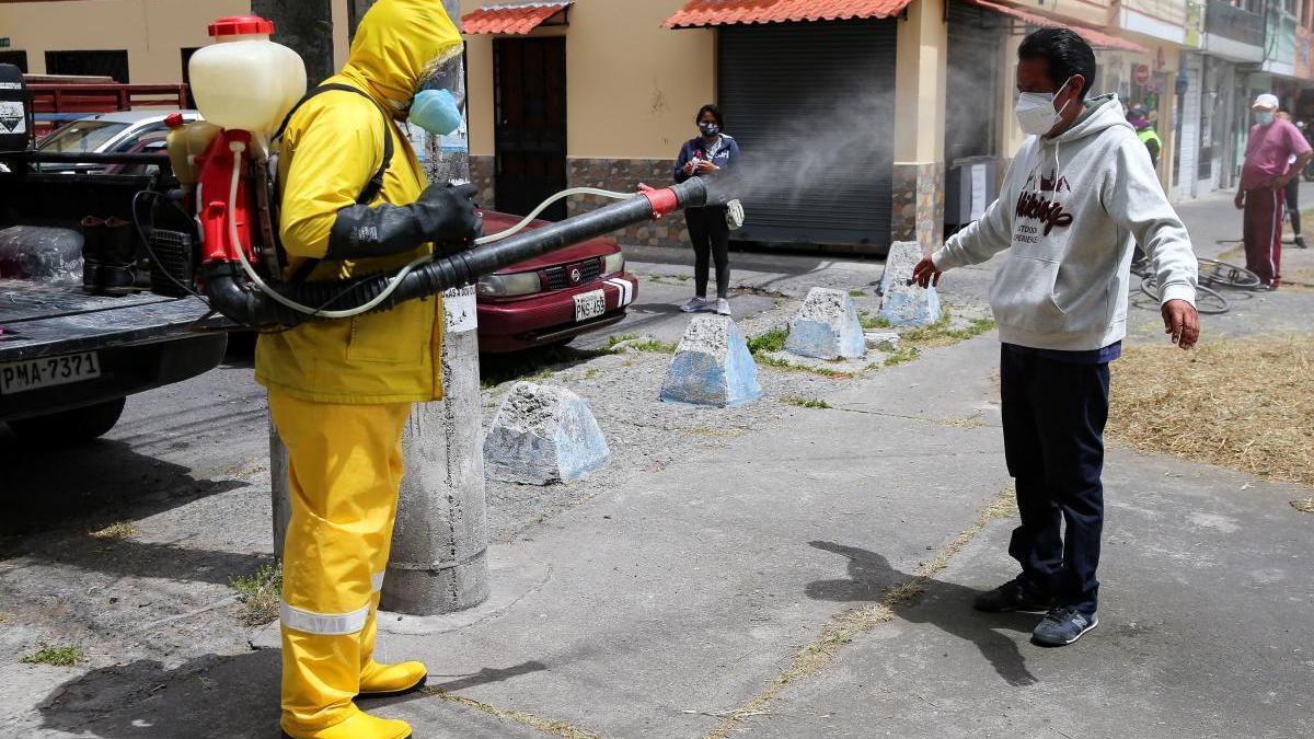 Un trabajador desinfecta a un hombre en Quito (Ecuador).