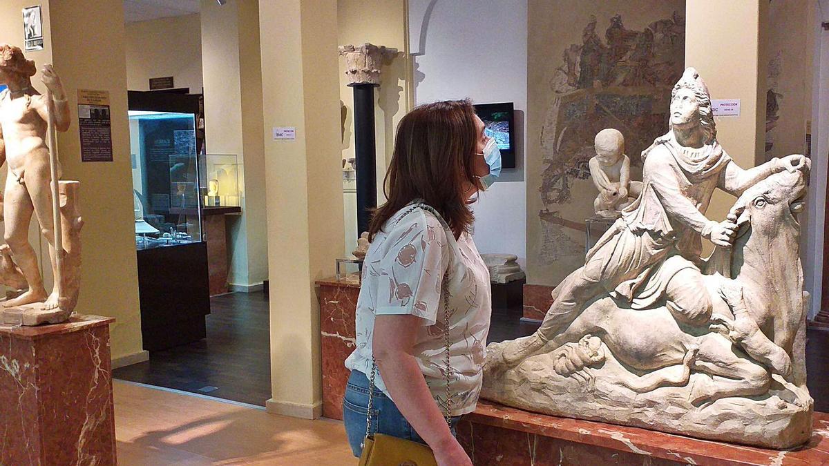 Una visitante observa la escultura del Dios Mitra en el Museo Arqueológico de Cabra.
