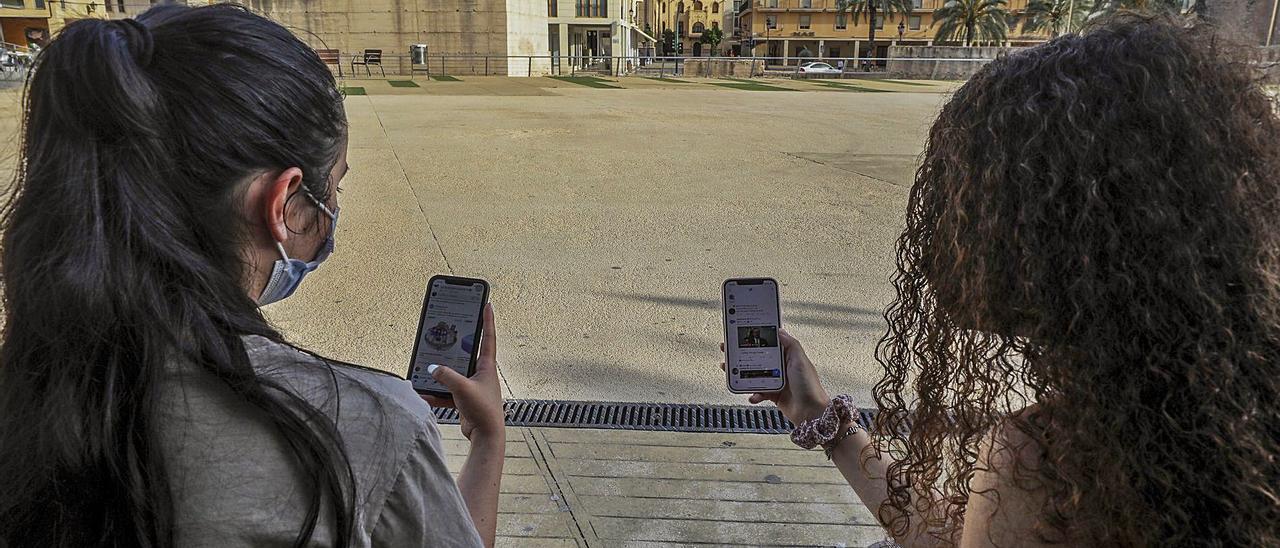 Dos jóvenes ilicitanas consultan las redes sociales a través de sus teléfonos móviles, en una imagen captada esta semana.   ANTONIO AMORÓS