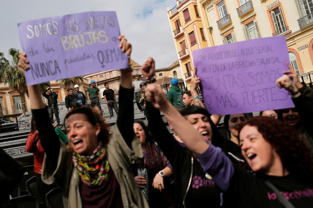 Workers watch as women take part in a protest at ...