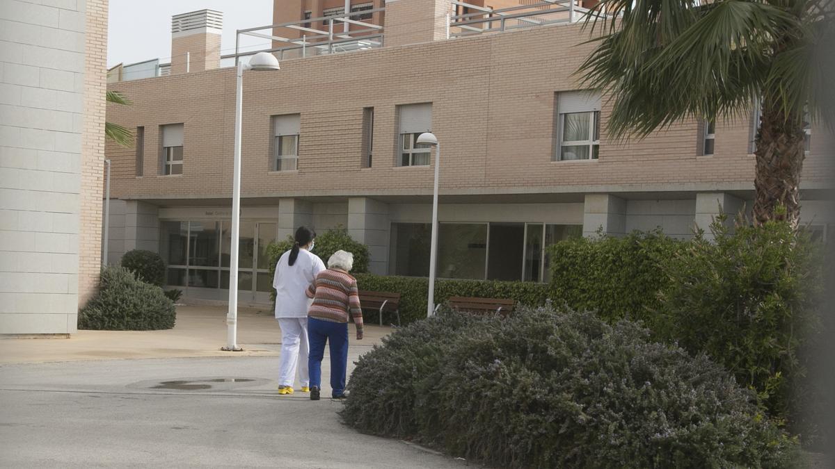 Una auxiliar de Enfermería acompaña a una residente de un geriátrico de Alicante.