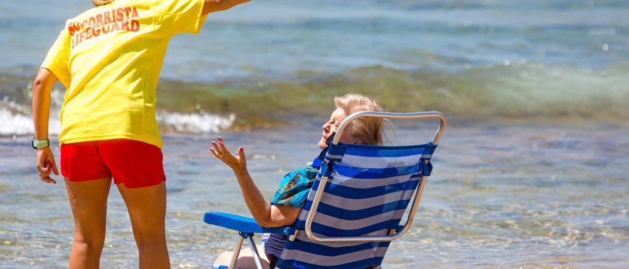 Un socorrista da indicaciones a una señora en las playa de Levante de Benidorm