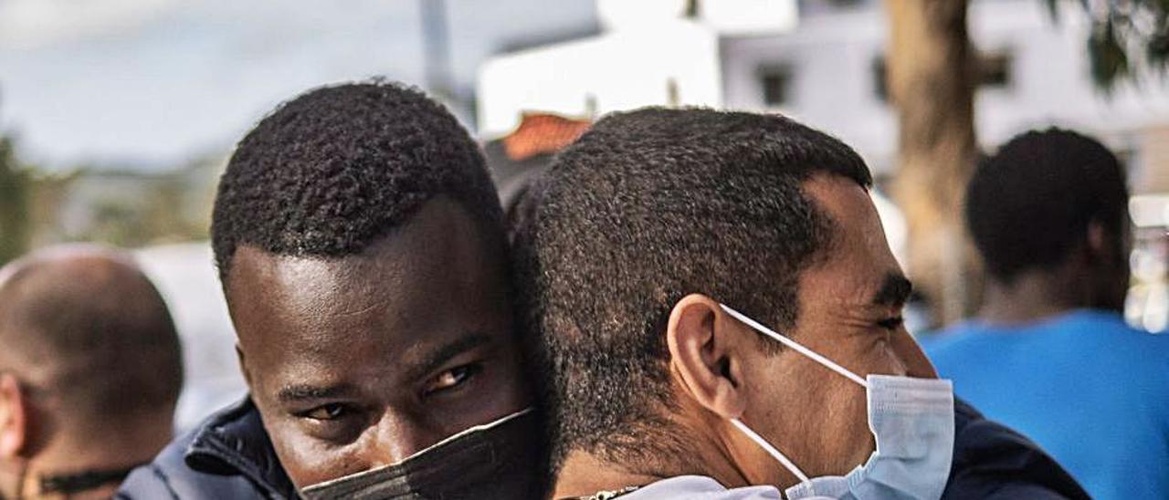 Dos migrantes se abrazan en la puerta de un campamento.