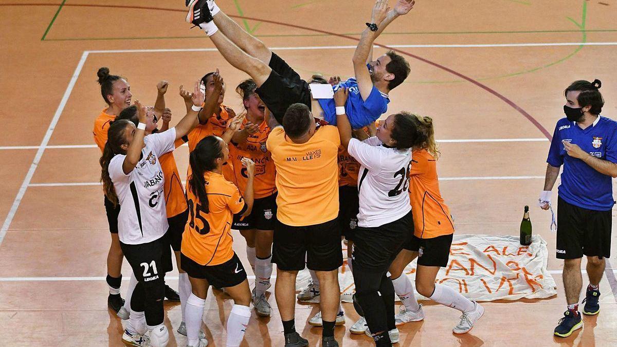 Las jugadoras del Viaxes Amarelle mantean a su entrenador, Jorge Basanta, tras lograr el ascenso a Primera.