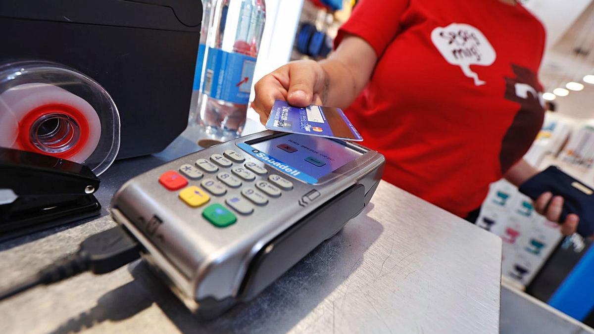 Una mujer paga con tarjeta de crédito en un establecimiento de la ciudad.