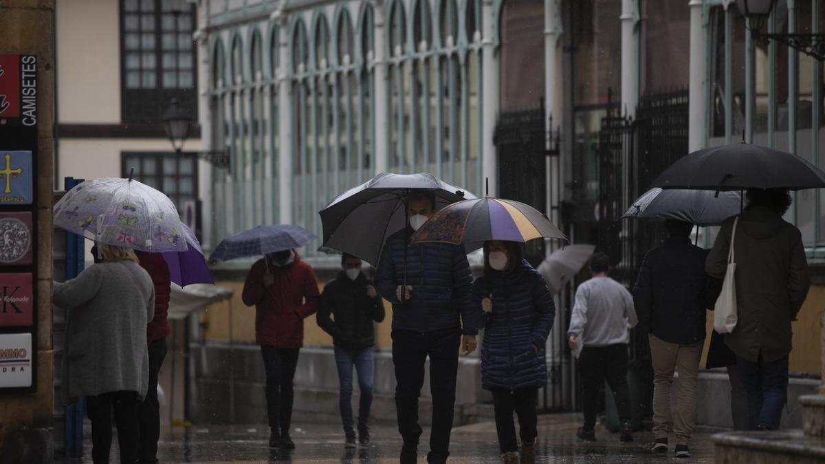 Gente en Oviedo paseando bajo la lluvia. MIKI LÓPEZ