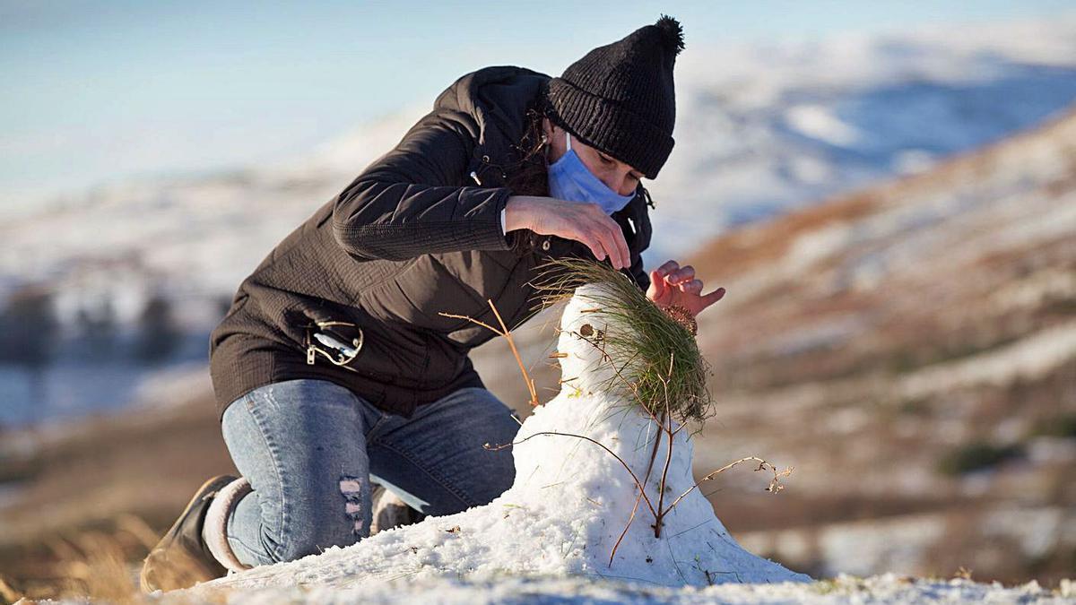 Una joven, haciendo un muñeco de nieve en Glasgow. |   // EFE