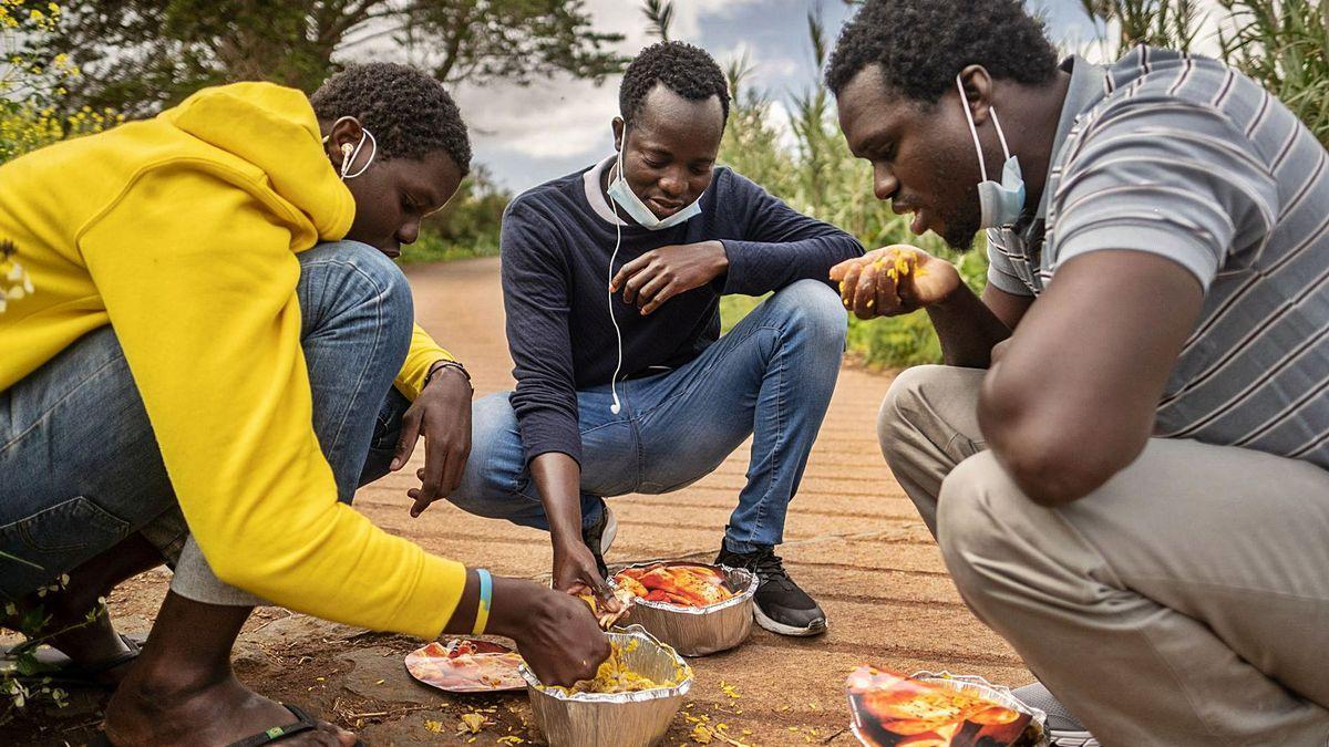 Migrantes comiendo arroz ofrecido por una empresa solidaria en el exterior del campamento de Las Raíces.
